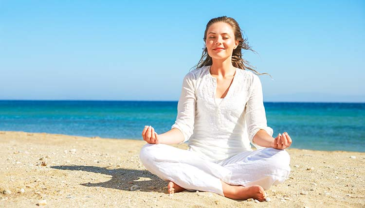 Woman meditating in Equilibrium on the beach